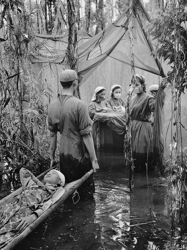 Камбоджийскую партизанку Дахн Сон Хоул несут в госпиталь, который соорудили на болоте (1970г.)