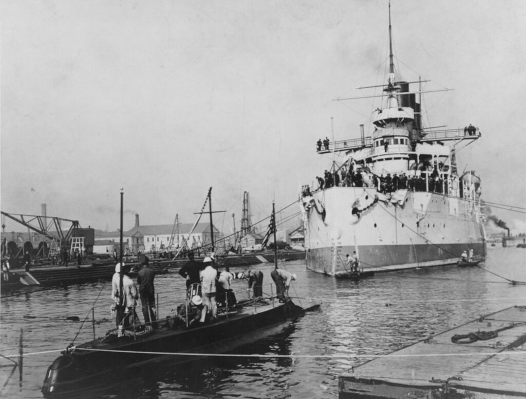 USS Holland (Submarine Torpedo Boat # 1) At the New York Navy Yard, Brooklyn, NY, in October 1901. In the background is the Russian battleship Retvizan, then nearing final completion.