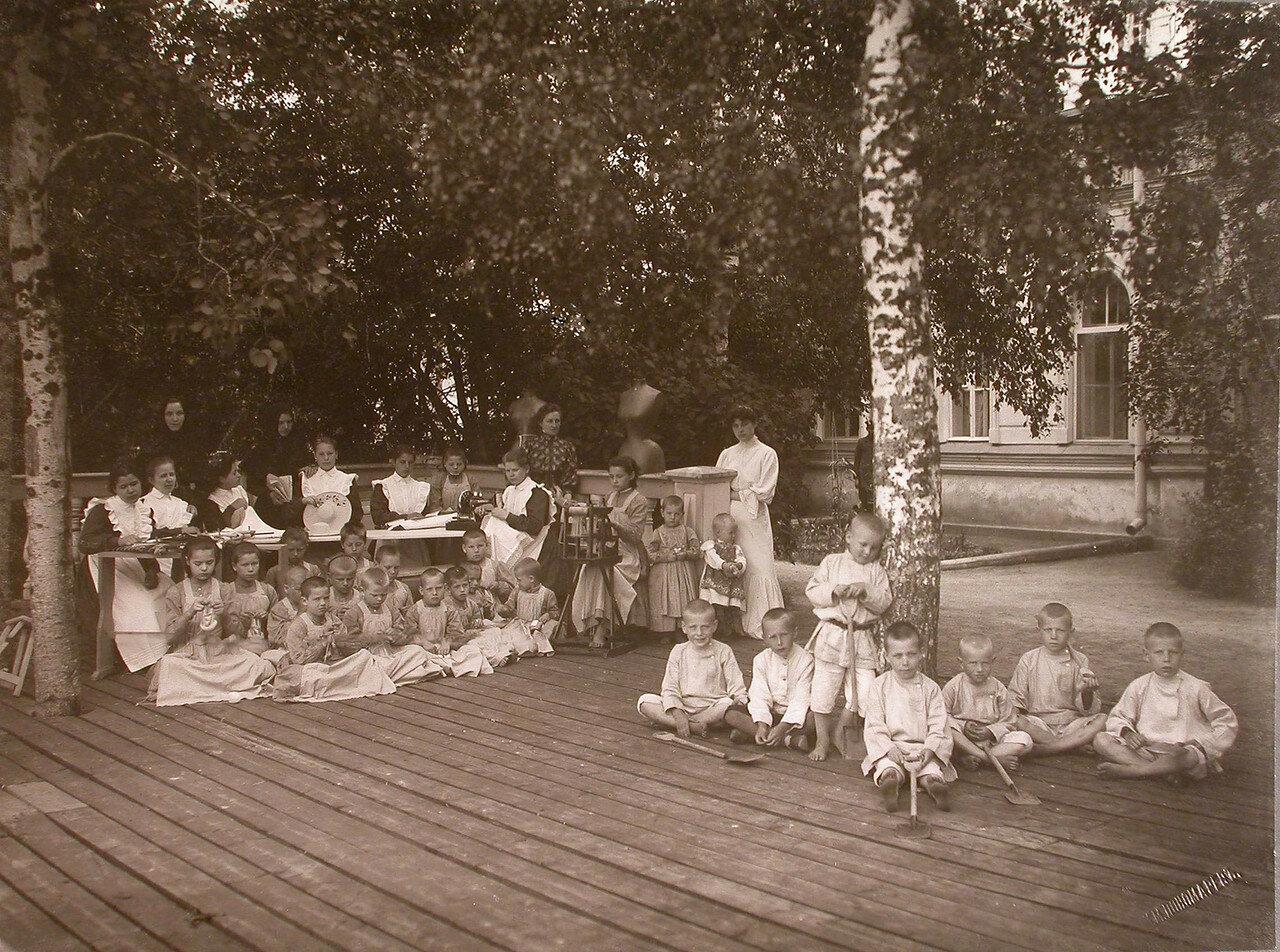 18. Группа детей во время занятий рукоделием у здания приюта