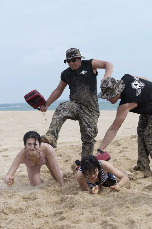 Trainers engage trainees dressed in swimming suits as they crawl on beach during training session in Sanya