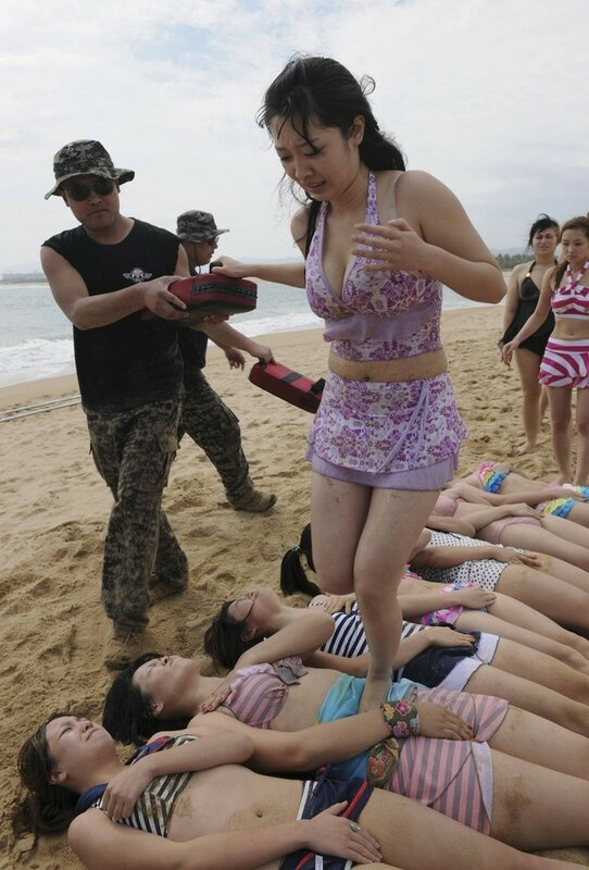 A trainee dressed in swimming suit steps on stomachs of other trainees with help of trainer during training session in Sanya