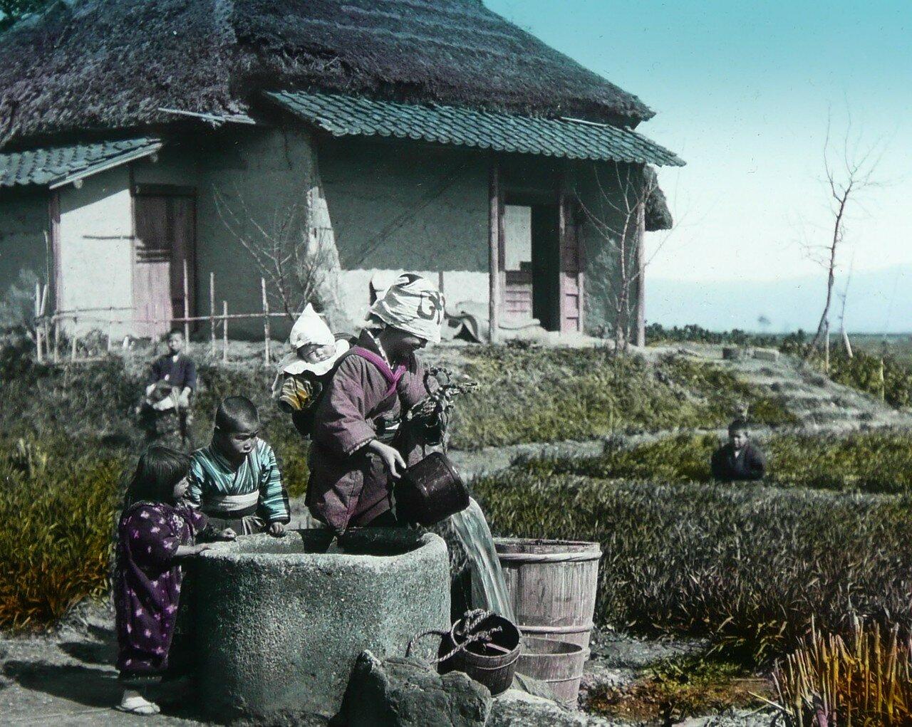 Мать набирает воду из колодца