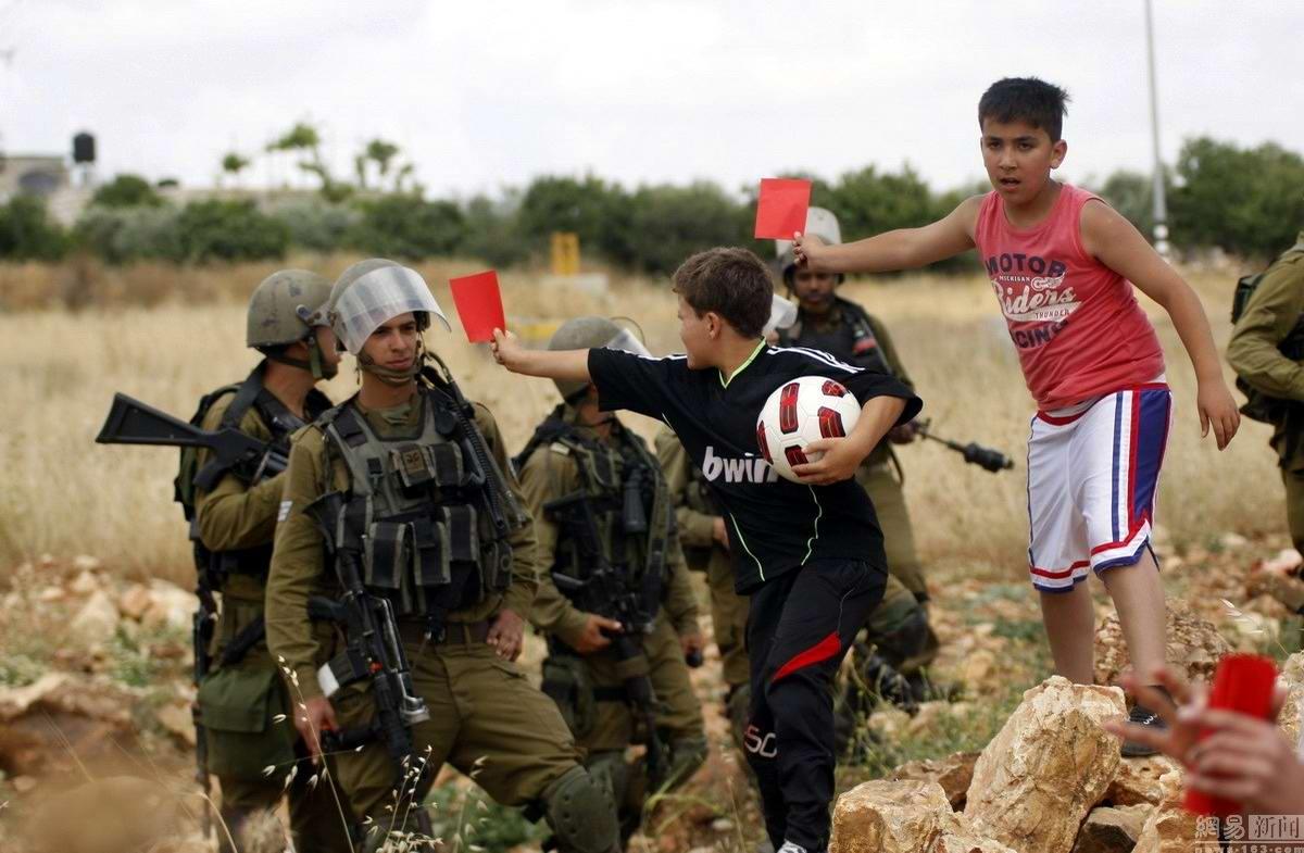 Околофутбольные страсти: Палестинские дети показывают красные карточки израильским солдатам (1)