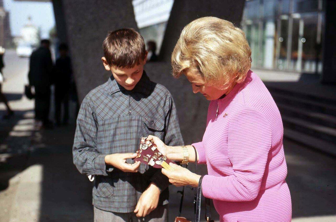 07. У входа в гостиницу  «Ангара». Мальчик предлагает Филисс значки с изображением Ленина