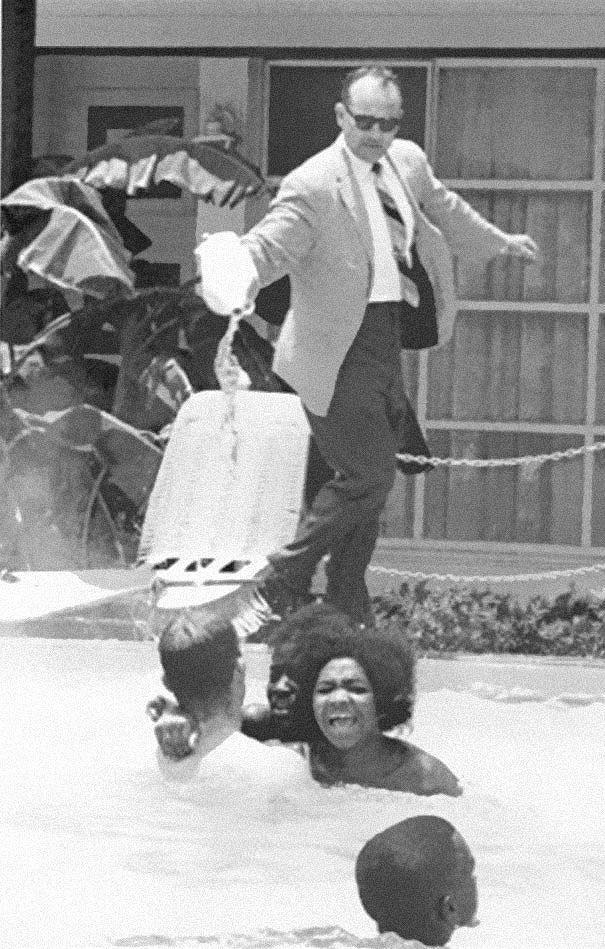 25. Владелец отеля выливает кислоту в бассейн, в котором плавают темнокожие, ок. 1964 года.