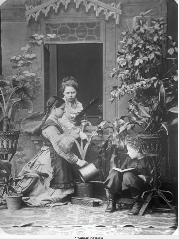 Пелагея Васильевна Дзержинская поливает цветы, справа – Андрей Карелин с книгой, у окна – Людмила Карелина