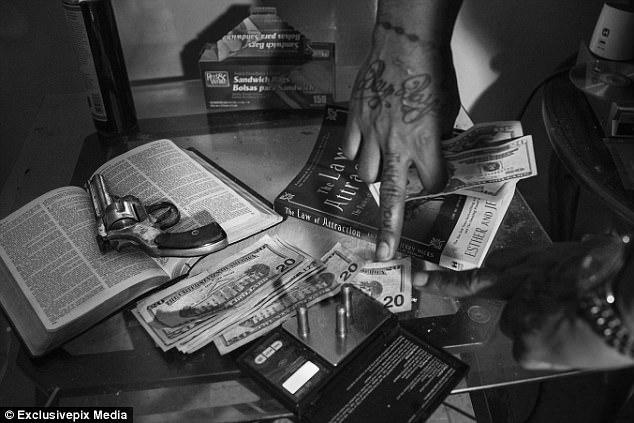 Teflon показывает на стол, где лежит пистолет, Библия, пули, наркотики и деньги. Наркотики и насилие