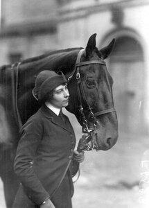 Наездница в амазонке с лошадью у конюшни.