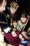 Епископ Зарайский Меркурий причащает детей.