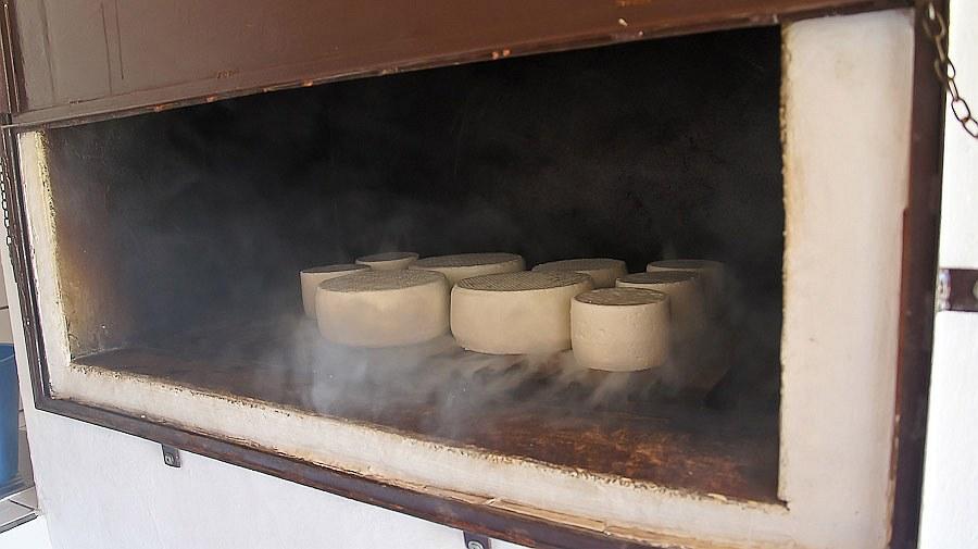 Поливает водой и сыр, чтобы не сгорал и лучше коптился.