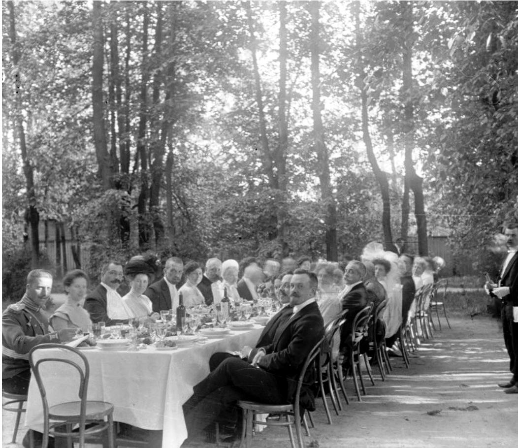 Группа людей за праздничным столом на природе