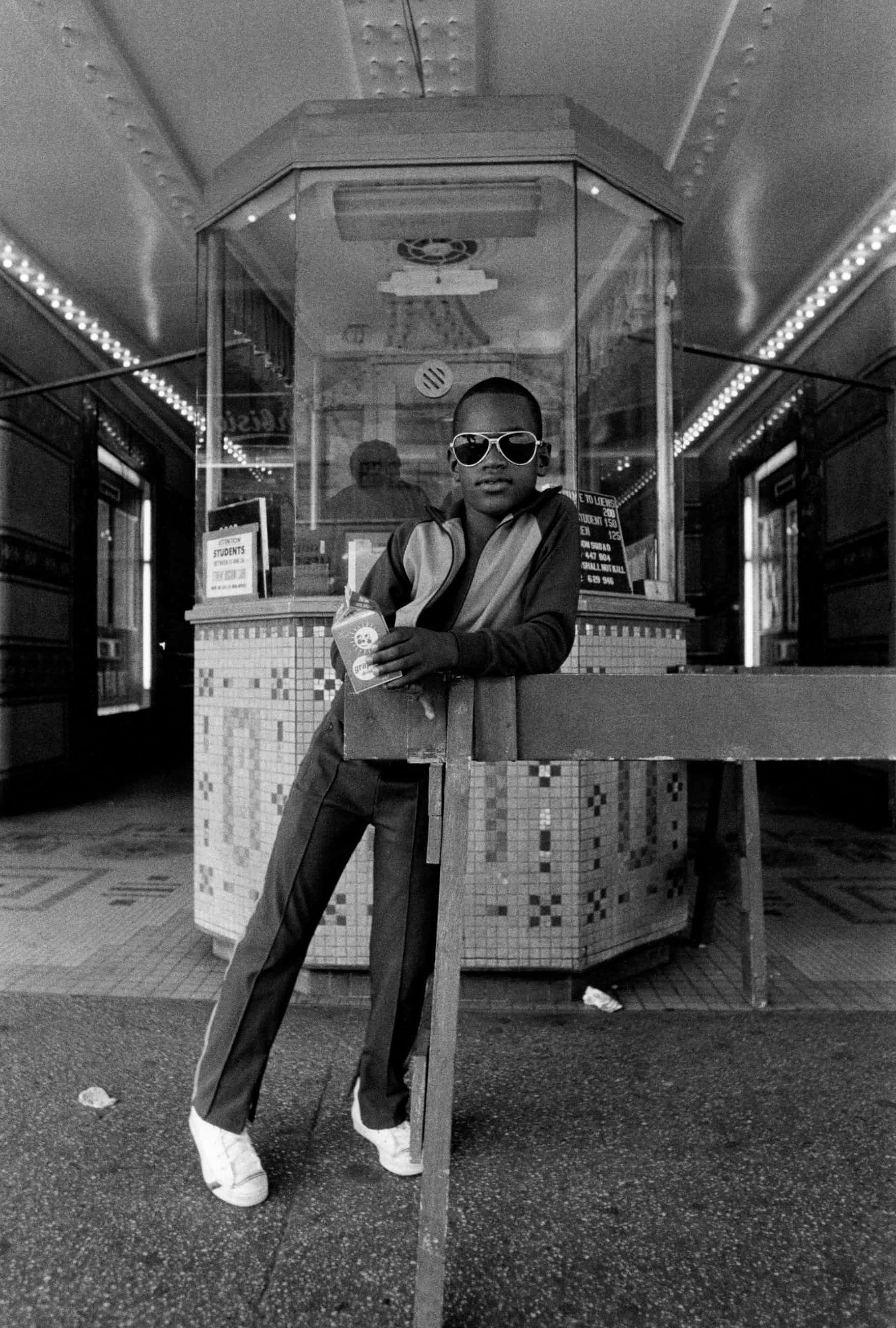 A boy in front of the Loew's 125th Street movie theatre, 1976 / Photograph: Dawoud Bey/Courtesy of S
