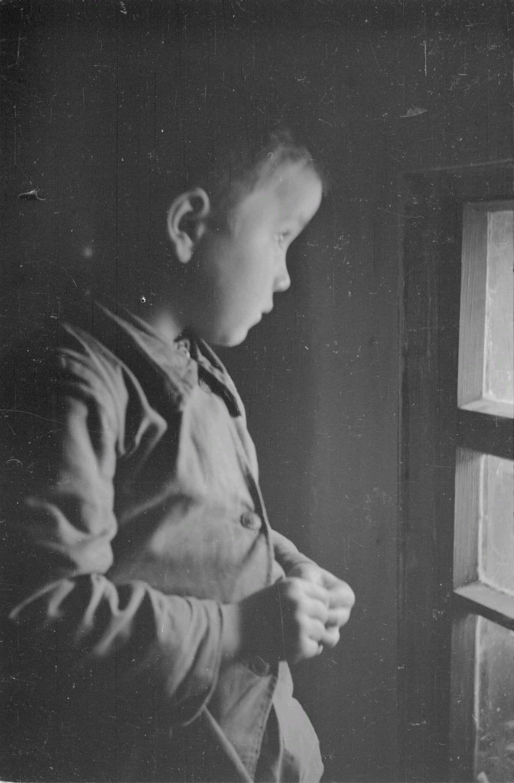 Маленький мальчик в окне крестьянского дома