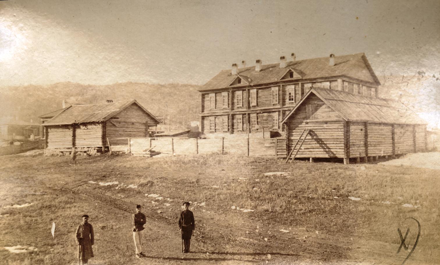 29. Два охранника с каторжанином на фоне тюремного поселения