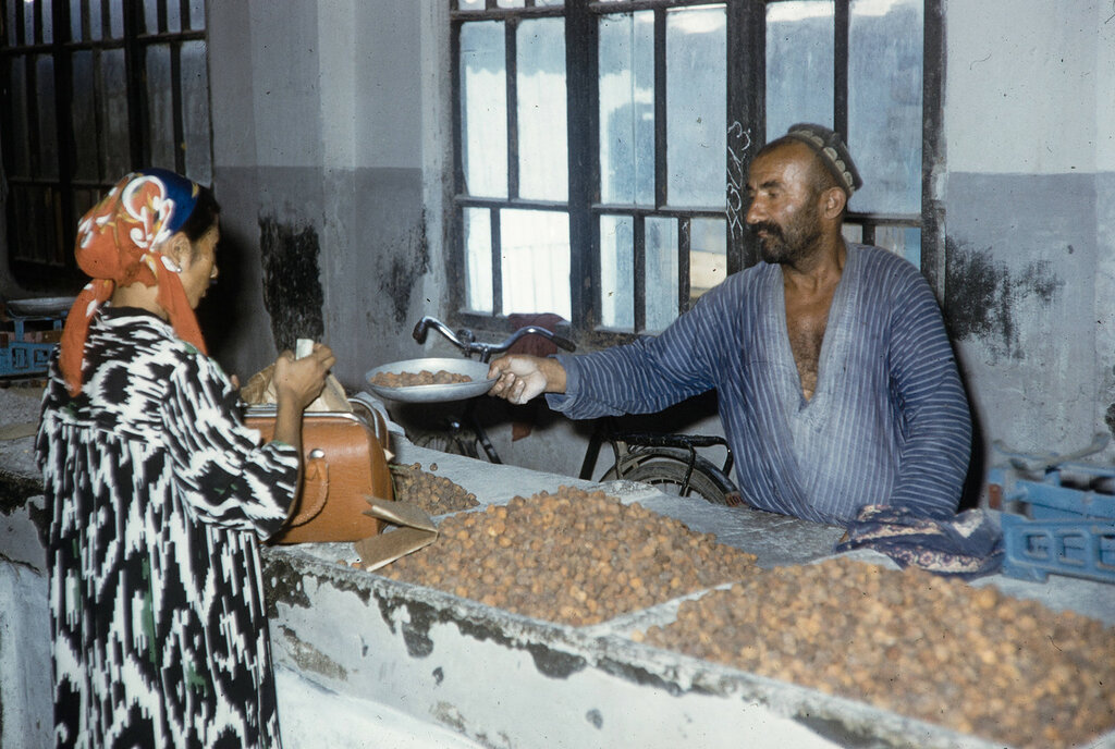 Uzbekistan, merchant selling goods to customer at Samarkand market