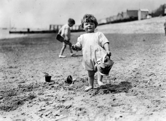 Полицейский измеряет у девушки на пляже длину купальника на соответствие его размеров устано