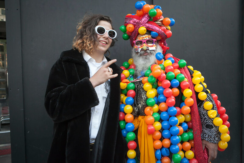 LONDON, ENGLAND - September 15, 2017 a man in a black fur coat of artificial fur with a man in a suit of plastic colored balls posing during the London Fashion Week. outside Eudon Choi