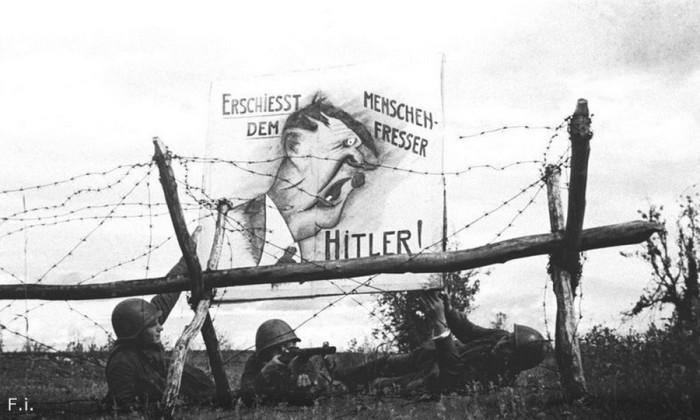 Бойцы рабоче-крестьянской Красной армии вывешивают карикатуру на Гитлера на передовой. Северо-Западн