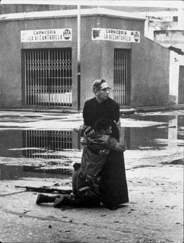 Пуэрто-Кабельо, Венесуэла. Капеллан Луис Мария Падильо держит на руках солдата-лоялиста (его имя Луи