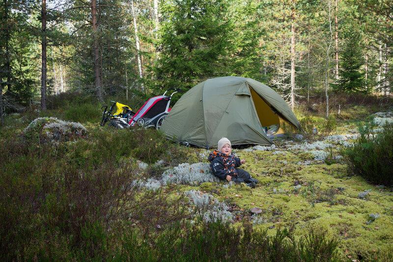 ребенок в походе сидит у палатки