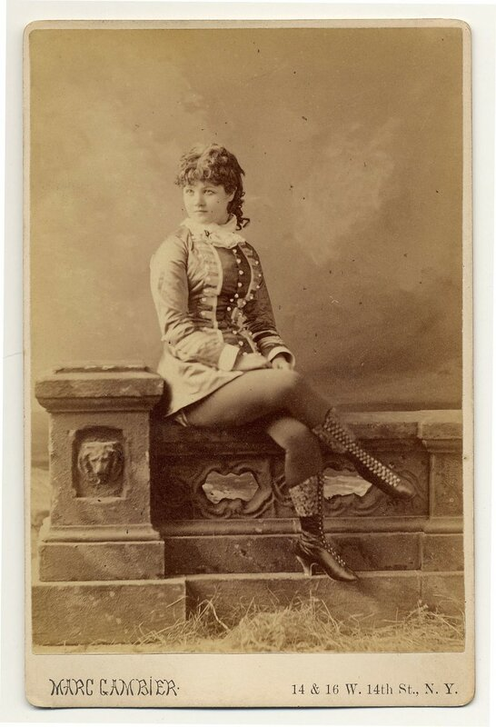 1890.  Minnie Marshall sitting on a stone sculpted fence, in short dress and boots.