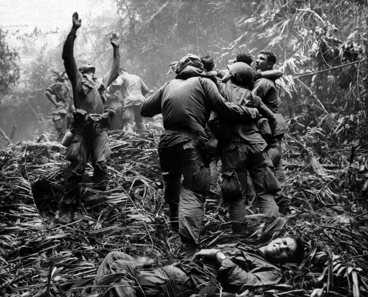 Сержант из 101-й воздушно-десантной дивизии армии США подает сигналы вертолетчикам, которые присланы для эвакуации раненых из джунглей в окрестностях города Хюэ