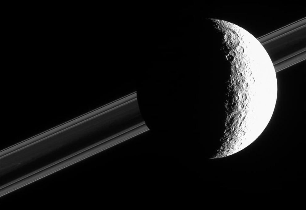 21. Мимас на фоне Сатурна. На освещённой стороне Мимаса отчётливо видны кратеры различных разме