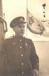 Гвардии инженер-капитан-лейтенант В.В. Коновалов у рубки на фоне флага. Полярный, лето 1943г.