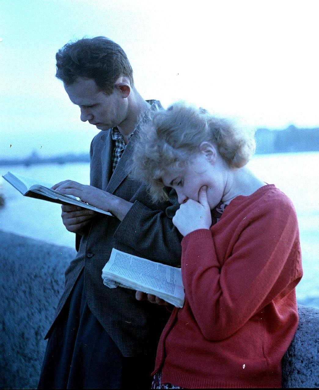 Пара читает на набережной Невы во время белых ночей
