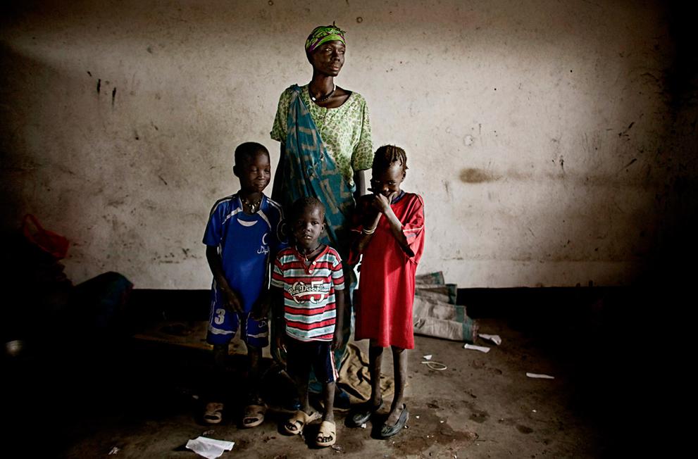 31. Мать с детьми, недавно бежавшие из дома, в классной комнате, превращенной в лагерь для беженцев,