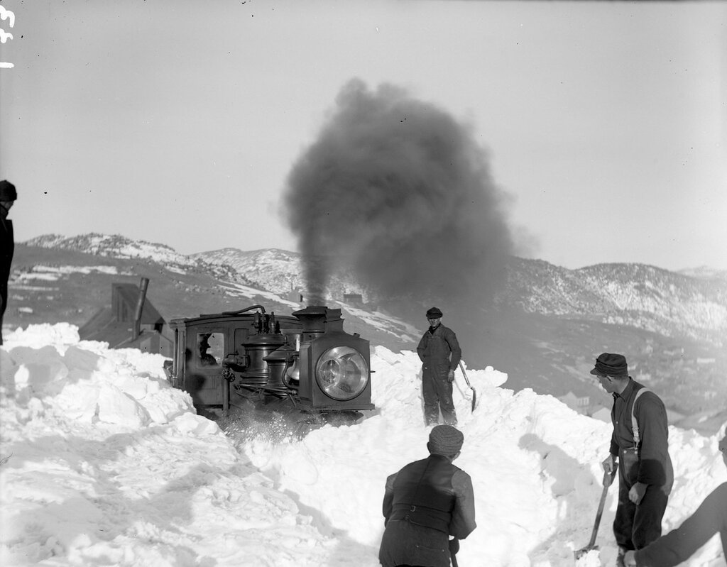 Men with shovels pose in deep snow beside a Gilpin Tramway locomotive near Central City (Gilpin County), Colorado, 1899.