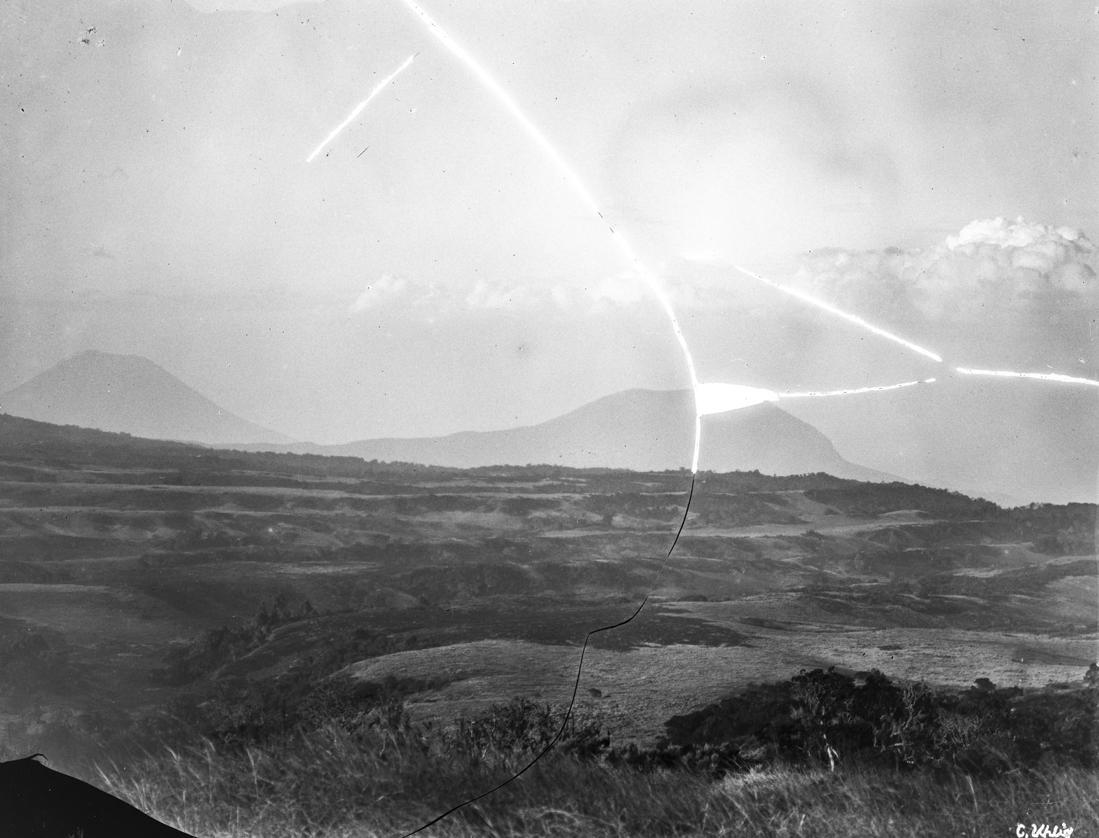 54. Высокогорные пастбища с остатками леса на плато выше уровня разлома. На заднем плане вулканы Ол-Доиньо-Ленгаи  (слева) и Керимаси (справа)