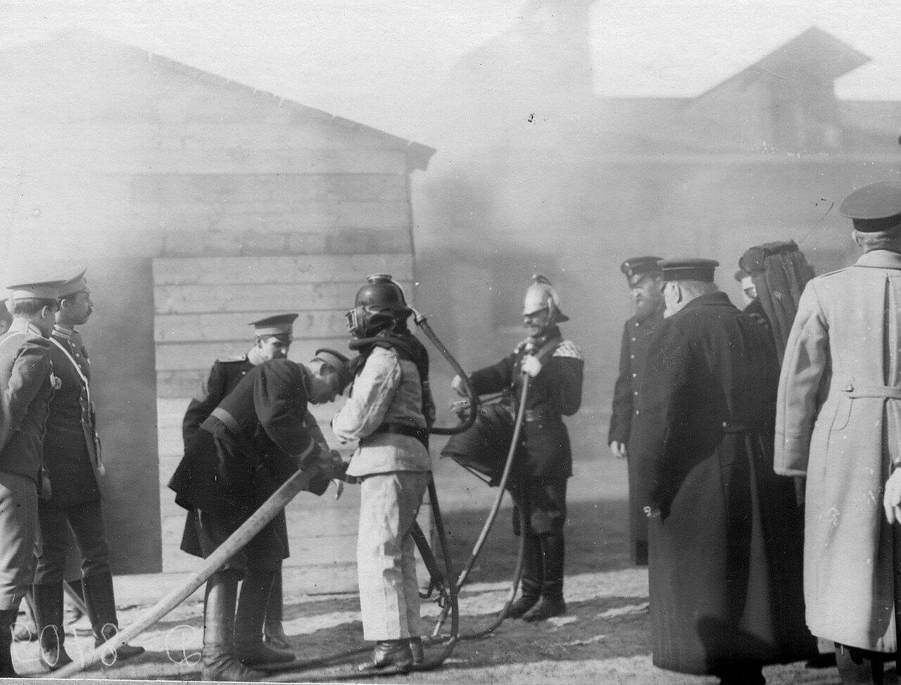 11. Великая княгиня Мария Павловна и сопровождающие ее лица наблюдают за работой пожарных в противодымном скафандре