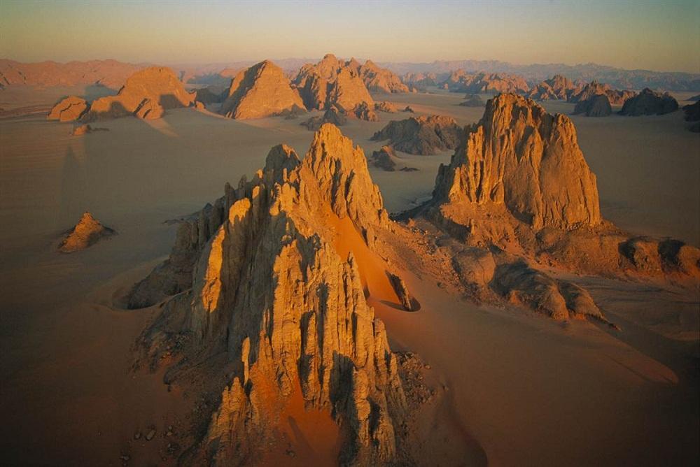 1. Долина Камасай в Чаде. Возвышенности песчаника пробиваются через оранжевые дюны в регионе Тибести
