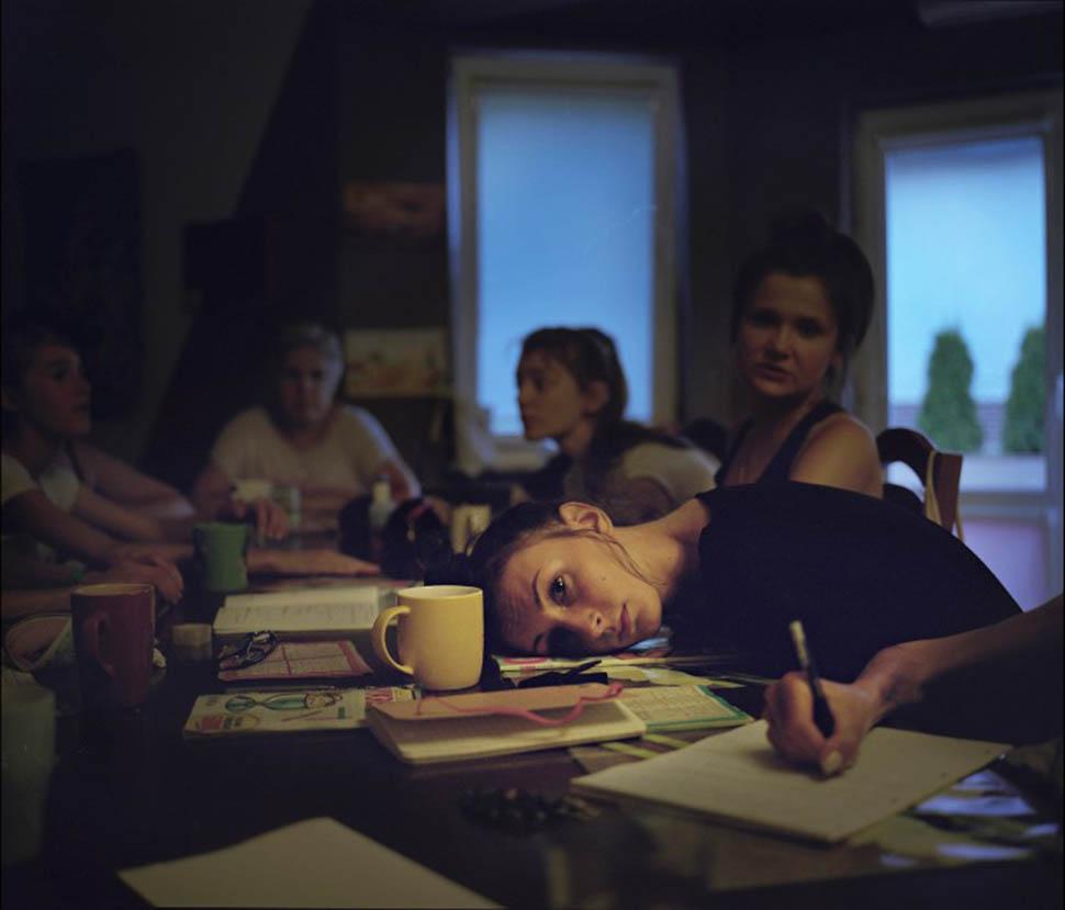 Каролина положила голову на стол, а другие девушки читают или решают кроссворды.