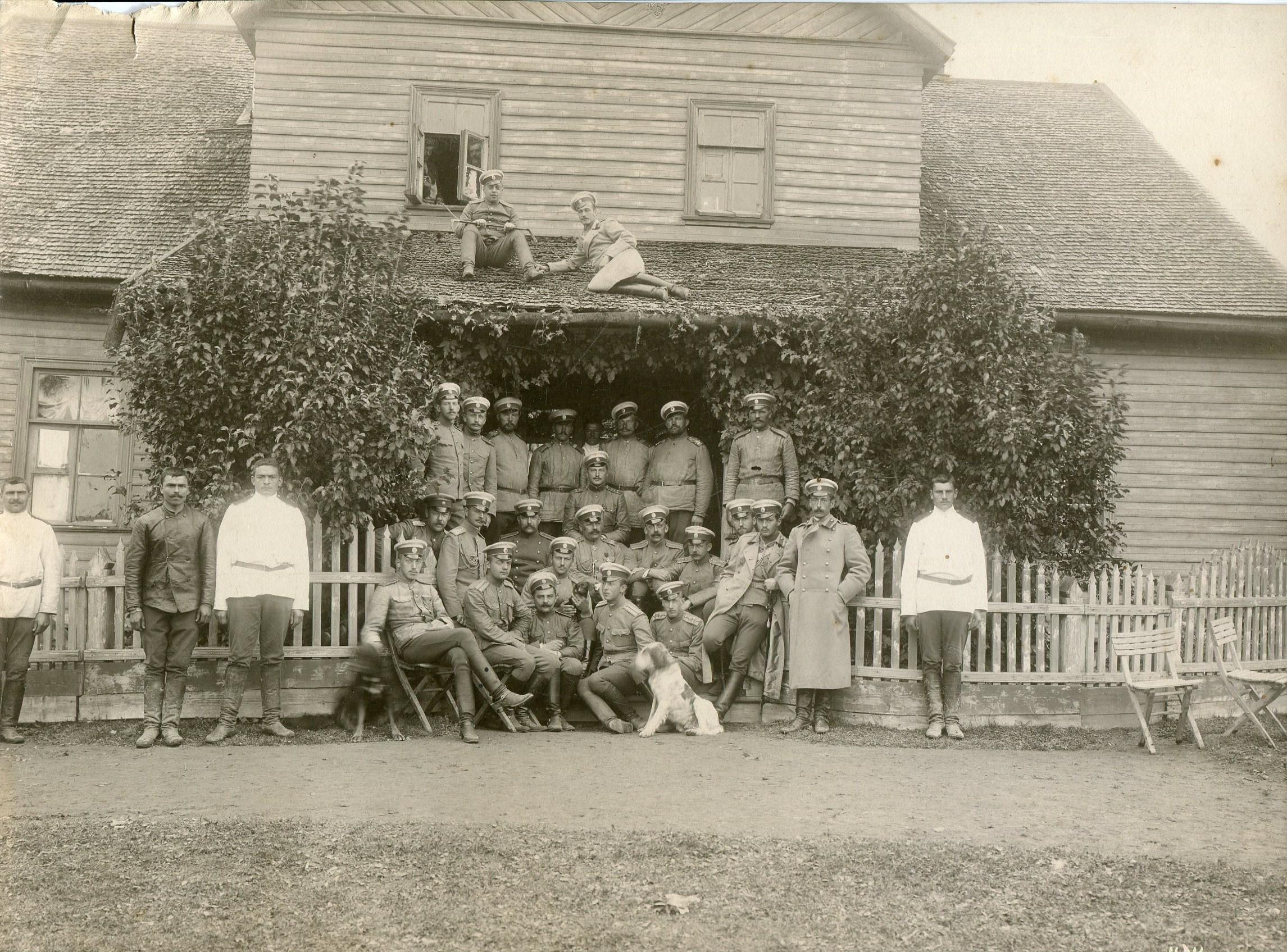 Фотография группы солдат и офицеров на фоне дома