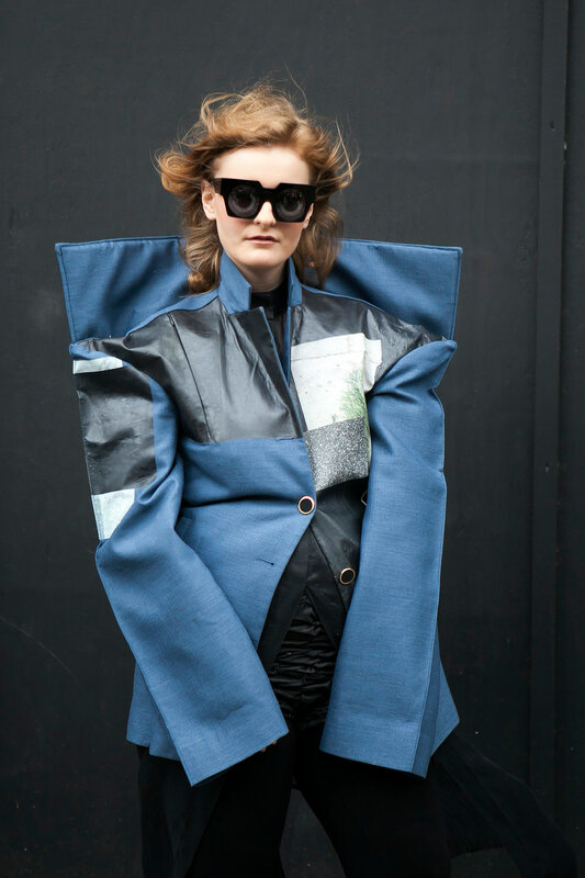 Beautiful and stylish woman in blue coat posing during the London Fashion Week. outside Eudon Choi