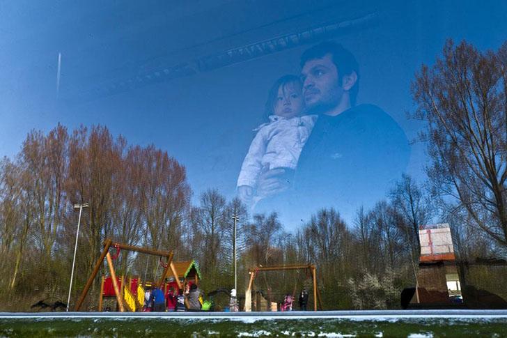 Афганский беженец с ребенком смотрят в окно на теперь закрытую тюрьму на северо-западе Нидерландов.