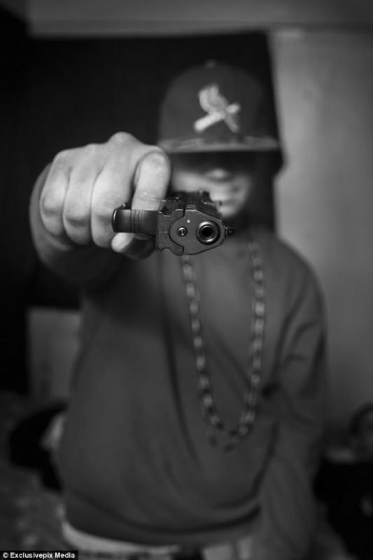 Murder держит в руках пистолет, который он купил за 250 долларов на улице после того, как его друга
