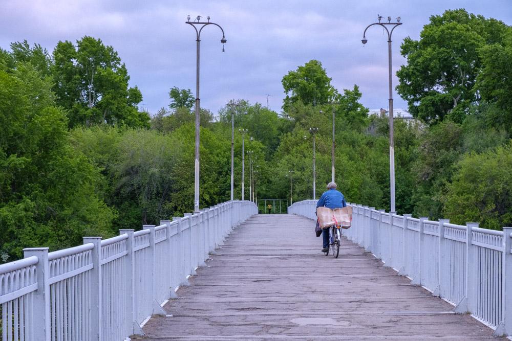 велосипедист едет по пешеходному мосту