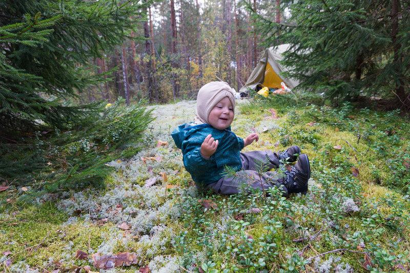 маленький ребенок сидит на мху в лесу рядом с палаткой