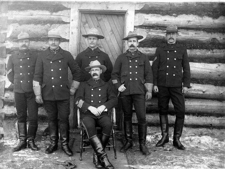 North-West_Mounted_Police_posed_in_front_of_log_cabin,_Dawson,_Yukon_Territory,_ca_1898_(HEGG_675).jpeg