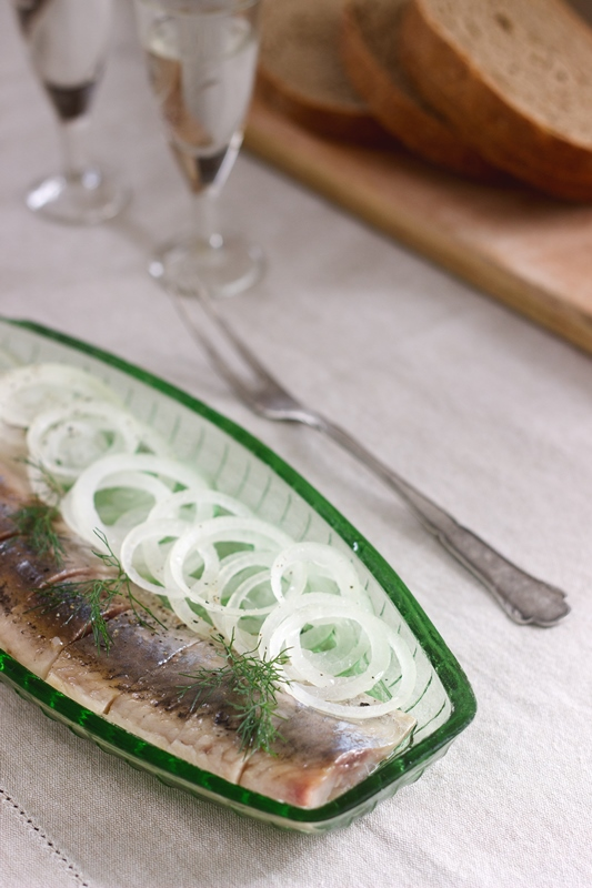 A herring with onions and dill in a glass plate, served with bread and vodka. Soviet life. Rustic style, selective focus.