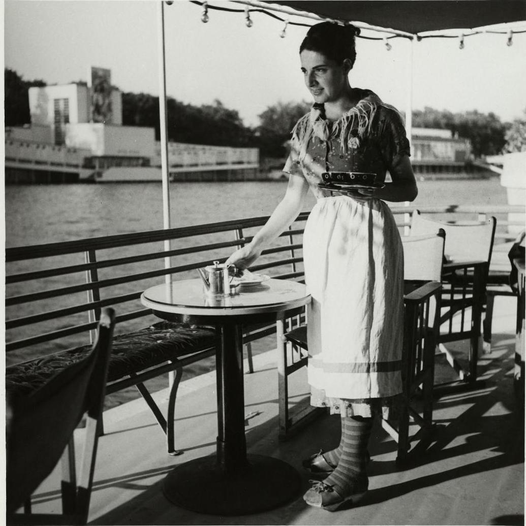 Павильон Швейцарии. Официантка в традиционном костюме в кафе, пришвартованном у подножия павильона