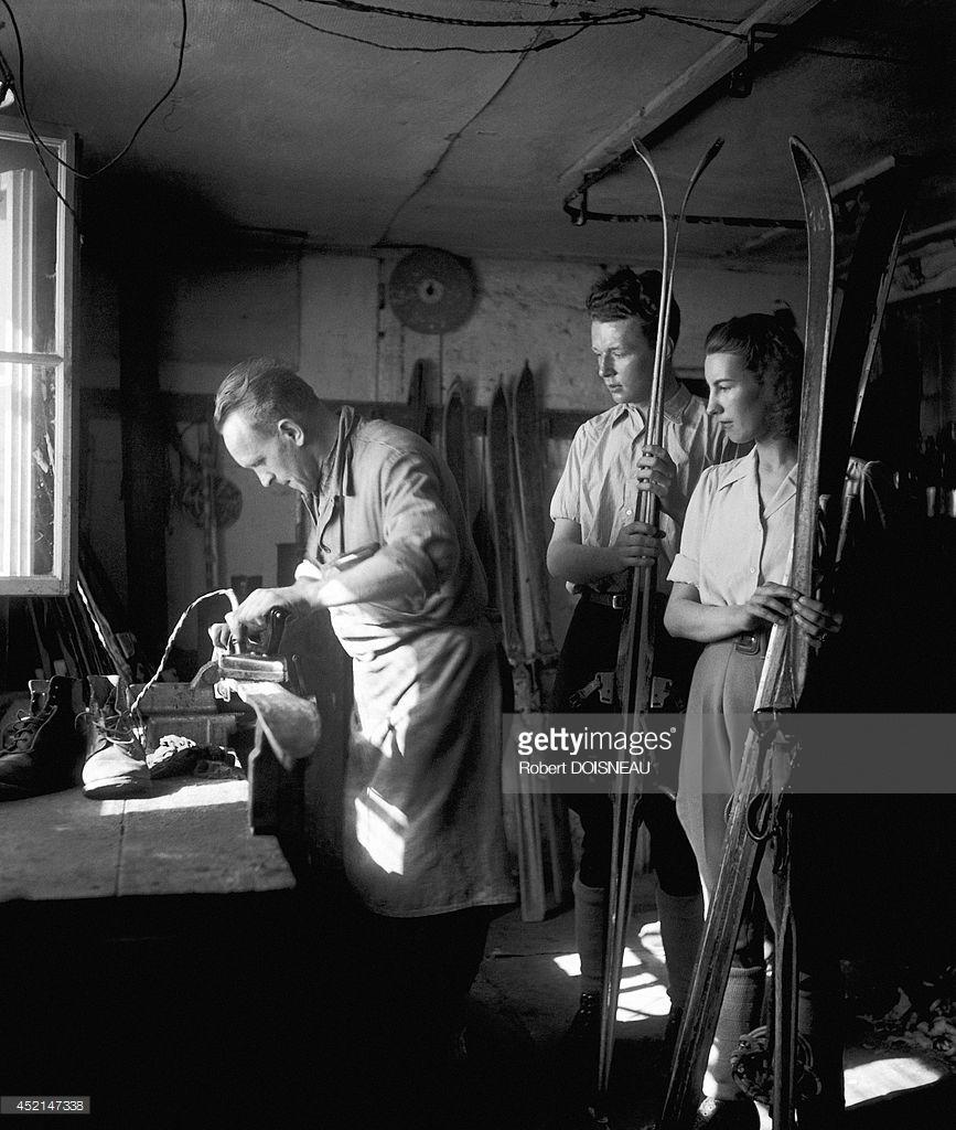 1946. Мужчина, смазывающий пару лыж и люди, ожидающие завершения работы в Тироле, Австрия