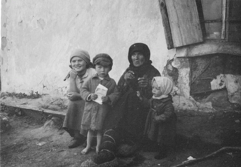 Старушка с молодой девушкой и двумя детьми возле дома.