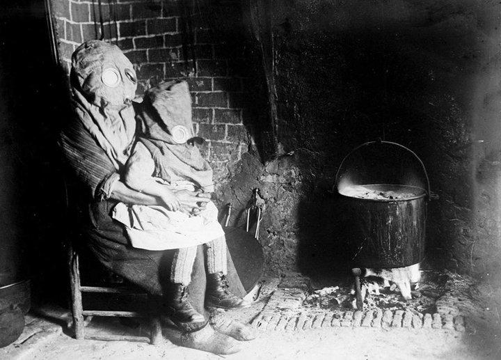 19. Мать с ребенком готовят еду в противогазах. Французская глубинка, Первая мировая война
