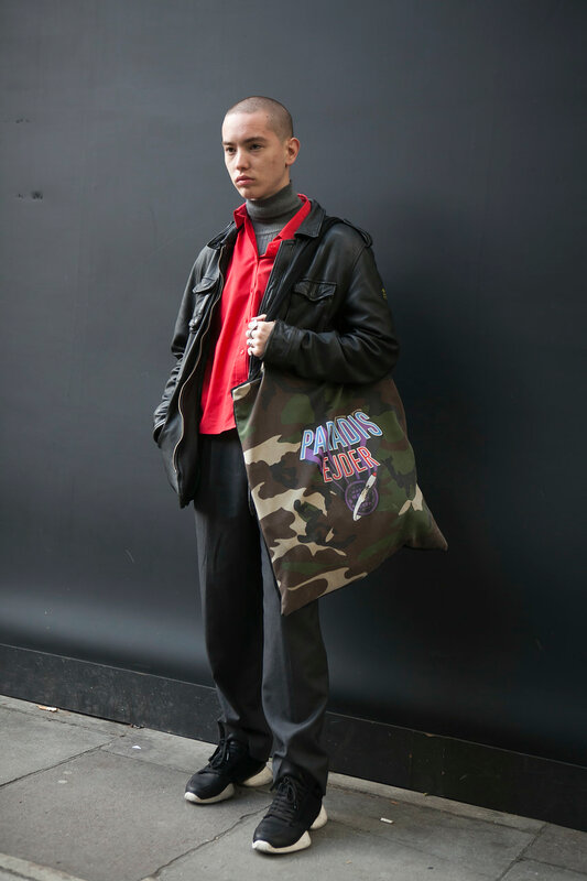 LONDON, ENGLAND - September 15, 2017 a short-cropped serious young man dressed in a sporting style posing during the London Fashion Week.