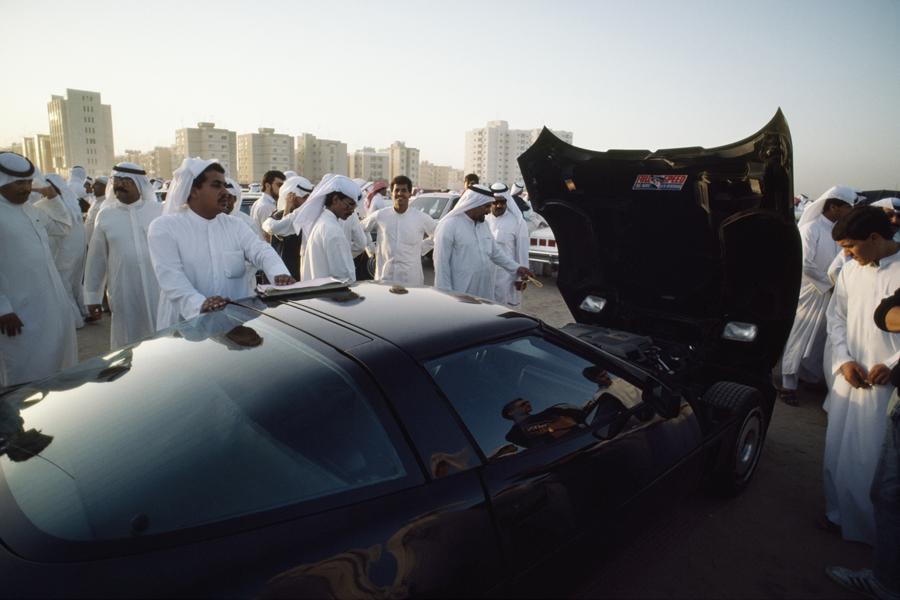 Покупатели осматривают спорткар Corvette на ежедневном автоаукционе в столице Кувейта, 1987.