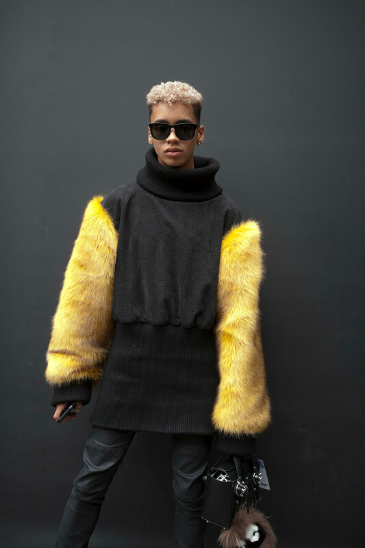 A young short-haired blond man in a black jumper with yellow sleeves made of faux fur